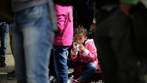 A girl drinks some juice after she arrived with other refugees at the train station of the southern German border town Passau, Tuesday, Sept. 15, 2015. - Sputnik International