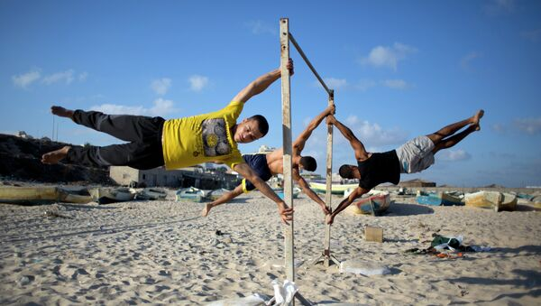 Members of Bar Palestine, a street workout team practice their skills during a training session on the beach of Gaza City - Sputnik International