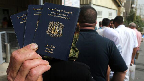 Syrian man holds his family's passports - Sputnik International