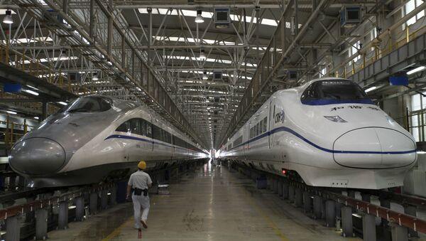 A worker walks between two bullet trains at a high speed railway maintenance station. - Sputnik International