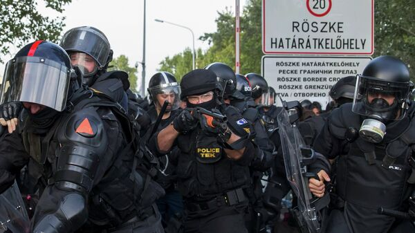 Hungarian riot police fight migrants at the border crossing with Serbia in Roszke, Hungary September 16, 2015 - Sputnik International