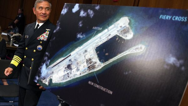 Adm. Harry B. Harris, Jr., US Navy Commander, U.S. Pacific Command walks past a photograph showing an island that China is building on the Fiery Cross Reef in the South China Sea - Sputnik International