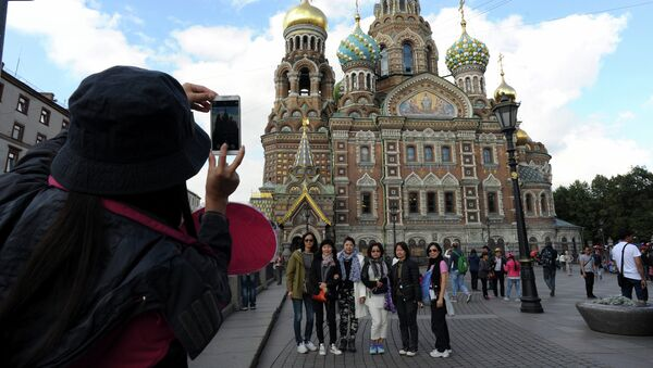 A picture taken on September 4, 2015 shows Chinese tourists as they have their photo taken in front of Church of the Savior on Blood  in central St. Petersburg. Drawn by its Communist past and a visa-free regime, Chinese tourists are flocking to Russia in droves as it develops new routes touting red tourism - Sputnik International