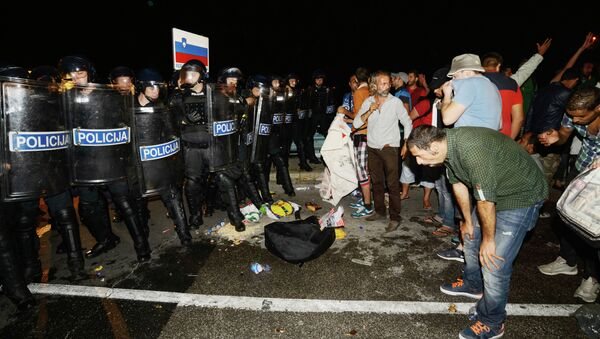 Migrants react after pepper spray was used in a small village of Rigonce in Slovenia, a small border crossing point to Harmica, Croatia, on September 18, 2015 - Sputnik International