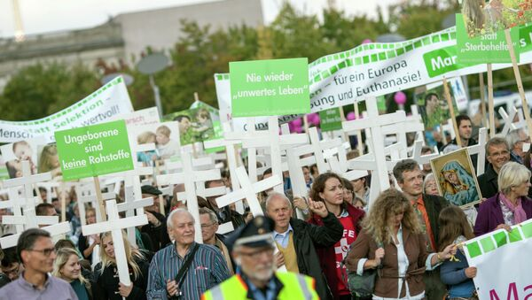 Supporters of christian group Pro Life carry crosses and hold a banner that reads (L) Unborn are no commodity as they protest against abortion in Berlin, Germany on September 21, 2013 - Sputnik International