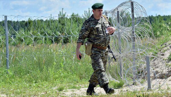 A Ukrainian border guard patrols on July 2, 2015 along the barbed wire fence on the Senkivka border post - Sputnik International