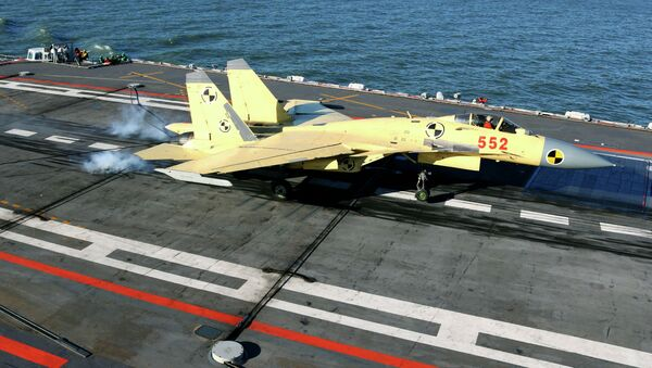 In this undated photo released by China's Xinhua News Agency, a carrier-borne J-15 fighter jet lands on China's first aircraft carrier, the Liaoning - Sputnik International