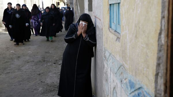 A woman mourns for the Egyptian Coptic Christians captured in Libya and killed by militants affiliated with the Islamic State group, outside of the Virgin Mary church in the village of el-Aour, near Minya, 220 kilometers (135 miles) south of Cairo, Egypt, Monday, Feb. 16, 2015 - Sputnik International