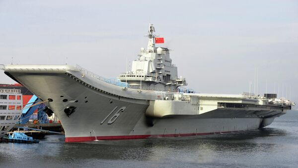 In this photo released by the Xinhua News Agency, Chinese aircraft carrier Liaoning berths in a port. China formally introduced its first aircraft carrier into service on Tuesday, Sept. 25, 2012 - Sputnik International