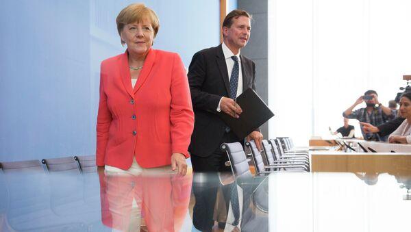 German Chancellor Angela Merkel, left, and government spokesman Steffen Seibert leave after Merkel's annual summer news conference in Berlin, Germany, Monday, Aug. 31, 2015 - Sputnik International