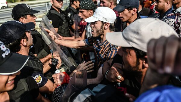 Migrants and refugees try to push a police barricade after they were blocked by Turkish riot police while walking towards Edirne on September 21, 2015 in Istanbul - Sputnik International