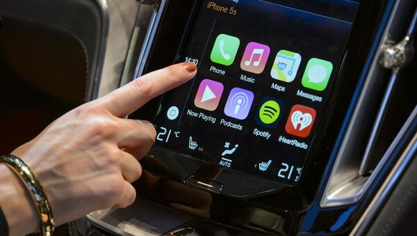 A visitor presses the new Apple's CarPlay touch-screen commands inside the Volvo Estate concept car displayed at the Swedish carmaker during the press day of the Geneva Motor Show in Geneva, on March 4, 2014. - Sputnik International