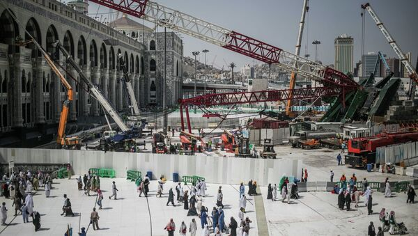 Muslim Pilgrims walk past the site of a crane collapse that killed over a hundred Friday at the Grand Mosque in the holy city of Mecca, Saudi Arabia, Tuesday, Sept. 15, 2015. - Sputnik International