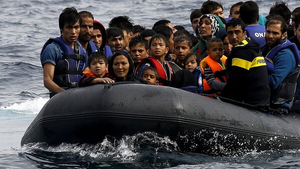 Exhausted Afghan migrants arrive on the Greek island of Lesbos in an overcrowded dinghy after crossing a part of the Aegean Sea from the Turkish coast September 22, 2015 - Sputnik International