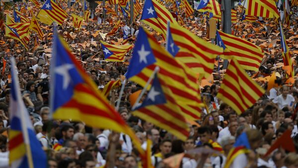 People wave pro-independence Catalan flags, known as the Estelada flag, during a rally calling for the independence of Catalonia, in Barcelona, Spain. - Sputnik International