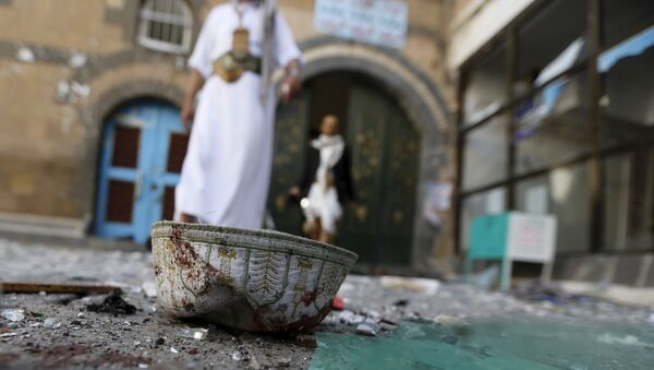 People walk past a headgear lying on the ground at the al-Balili mosque after two bombings at the mosque in Yemen's capital Sanaa September 24, 2015 - Sputnik International