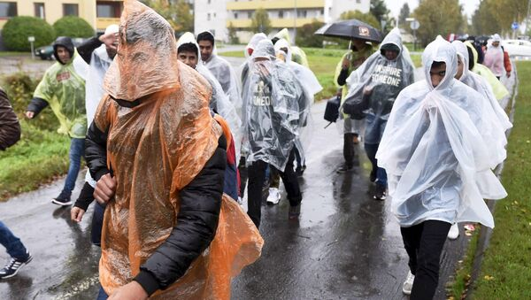 Refugees walked in heavy rain from a public transport centre to Lappia-building refugee reception centre in Tornio, northwestern Finland - Sputnik International