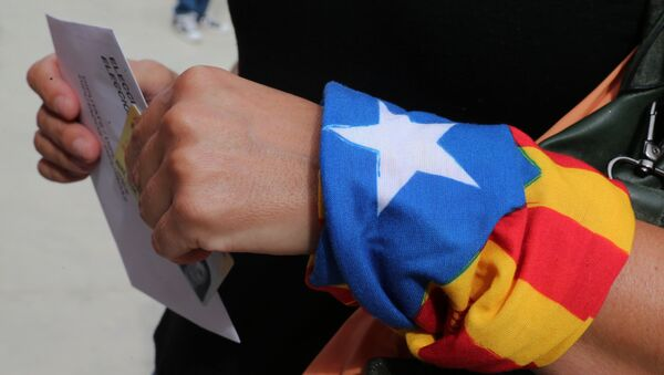 A woman with an Estelada (Catalan pro-independece flag) tied to her wrist waits for casting her ballot for the regional election at a polling station in Badalona on September 27, 2015 - Sputnik International