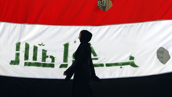 An Iraqi woman walks her national flag during a celebration marking the the departure of US troops from Iraq in Baghdad's Adhamiyah neighbourhood. File photo - Sputnik International