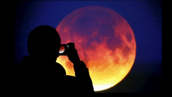 A man takes picture of the screen displaying the moon, appearing in a dim red colour, which is covered by the Earth's shadow during a total lunar eclipse in Warsaw, Poland September 28, 2015 - Sputnik International