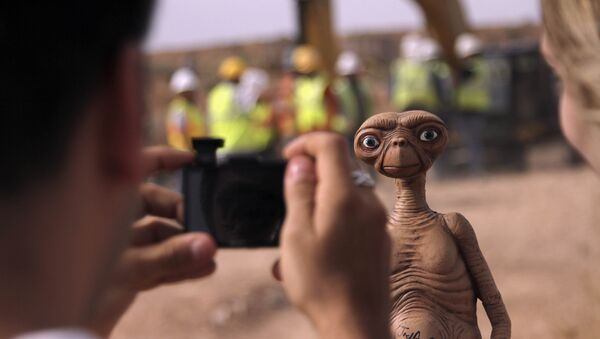 In this April 26, 2014 file photo, a man takes a photo of an E.T. doll in Alamogordo, N.M. Producers of a documentary dug in an southeastern New Mexico landfill in search of millions of cartridges of the Atari 'E.T. the Extra-Terrestrial' game that has been called the worst game in the history of video gaming and were buried there in 1983. - Sputnik International