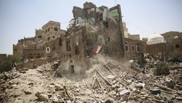 A man, left, stands guard amid the rubble of a house damaged in a Saudi-led airstrike in Sanaa, Yemen, Saturday, Sept. 19, 2015. - Sputnik International