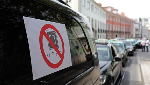 Taxis with signs against the Uber ride-hailing service clog a street in Lisbon while moving at a slow pace in protest, Tuesday, Sept. 8 2015 - Sputnik International