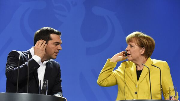 German Chancellor Angela Merkel (R) and Greek Prime Minister Alexis Tsipras hold their earpieces as they address a press conference following talks at the chancellery in Berlin, on March 23, 2015 - Sputnik International