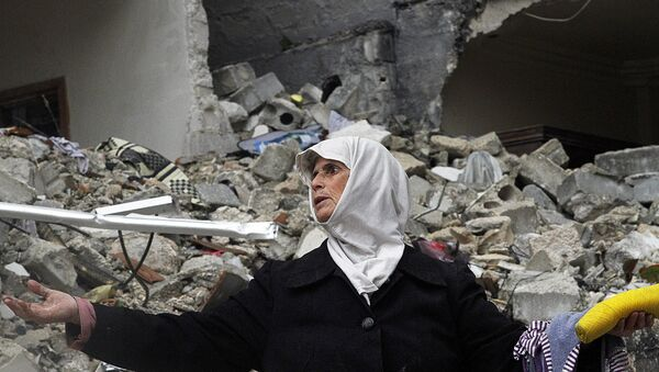In this Wednesday, Feb. 6, 2013 photo, a Syrian woman stands amid the ruins of her house which was destroyed in an airstrike by government warplanes a few days earlier, killing 11 members of her family, in the neighborhood of Ansari, Aleppo, Syria. - Sputnik International