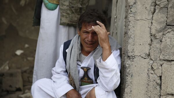 A man cries after some of his relatives were killed in a Saudi-led airstrike in Sanaa, Yemen, Monday, Sept. 21, 2015. - Sputnik International