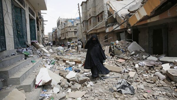 A woman walks amid the rubble of houses destroyed by a Saudi-led airstrike in Sanaa, Yemen, Monday, Sept. 21, 2015 - Sputnik International