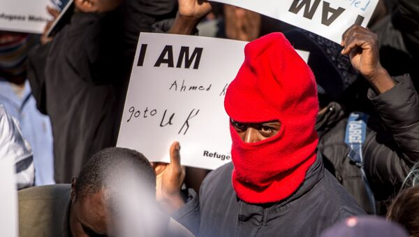 A migrant holds a placard reading 'I am Ahmed. Go to UK' as part of a rally of around 3000 migrants and members of associations aiding migrants including British associations, in the northern French port city of Calais (File) - Sputnik International
