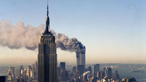 In this Sept. 11, 2001, file photo, the twin towers of the World Trade Center burn behind the Empire State Building in New York. - Sputnik International