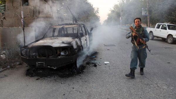 An Afghan policeman patrols next to a burning vehicle in the city of Kunduz, Afghanistan October 1, 2015 - Sputnik International