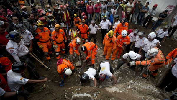 Rescue workers and firemen search for survivors at the the site of a landslide in Cambray, a neighborhood in the suburb of Santa Catarina Pinula, about 10 miles east of Guatemala City, Friday, Oct. 2, 2015. - Sputnik International