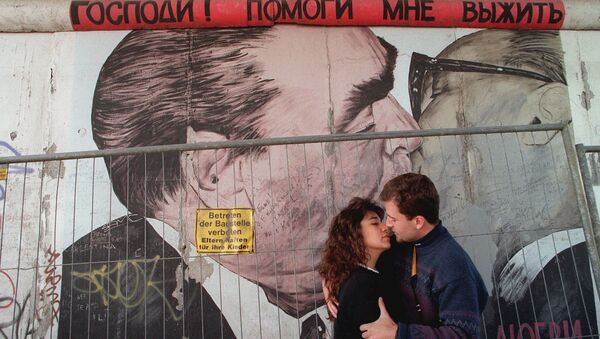 Two unidentified tourists kiss in front of a painting on one of the rare remaing parts of the Wall in Berlin, in October 1995 - Sputnik International