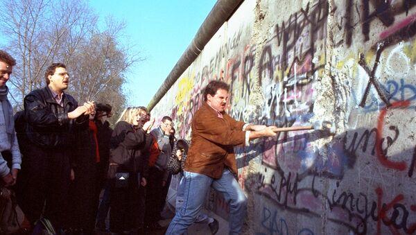 An unidentified West Berliner swings a sledgehammer, trying to destroy the Berlin Wall near Potsdamer Platz, on November 12, 1989, where a new passage was opened nearby - Sputnik International