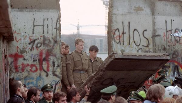 East German border guards look through a hole in the Berlin wall after demonstrators pulled down one segment of the wall at Brandenburg gate in this November 11, 1989 file picture - Sputnik International