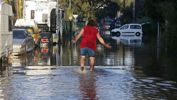 A man reacts as he wades through flood waters near cars after flooding caused by torrential rain in Biot, France - Sputnik International