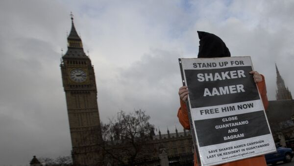 A hooded protester demonstrates for a Guantanamo detainee Shaker Aamer outside the Palace of Westminster in London, Wednesday, Jan. 15, 2014. - Sputnik International