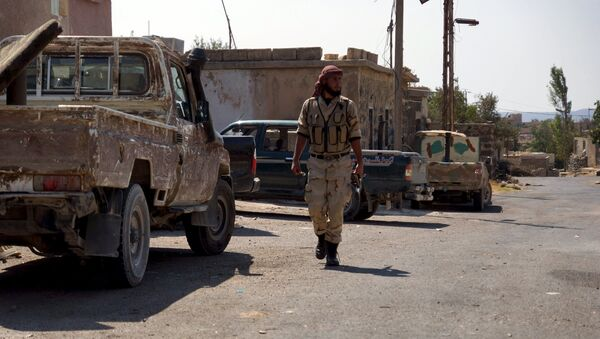 A Free Syrian Army fighter walks near military vehicles during what they said was preparations for an operation to strike at forces loyal to Syria's president Bashar Al-Assad in order to break a siege on the city of Beit Gin located in western countryside of Damascus in Deraa, Syria September 30, 2015 - Sputnik International
