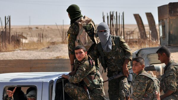 Fighters from the Kurdish People's Protection Units (YPG) sit in the back of a vehicle in the al-Zohour neighbourhood of northeastern Syrian city of Hasakeh on August 2, 2015, a week after Syrian troops and Kurdish fighters ousted the Islamic State group from Hasakeh - Sputnik International