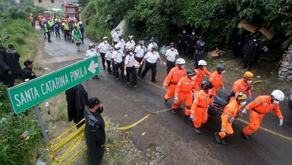 Rescue team members carry the bodies of mudslide victims toward the coroner's truck, in Santa Catarina Pinula - Sputnik International