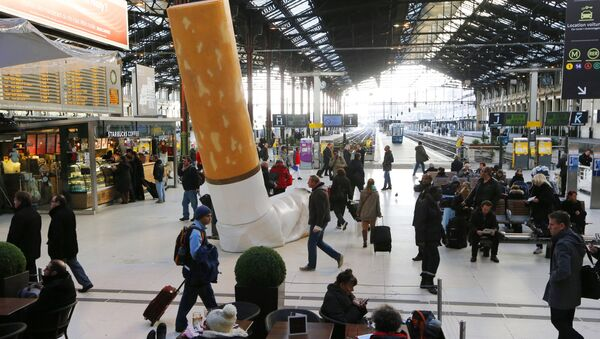 People pass by a giant mock-up discarded cigarette displayed on the ground at the Gare de Lyon railway station in Paris, on December 4, 2012. - Sputnik International
