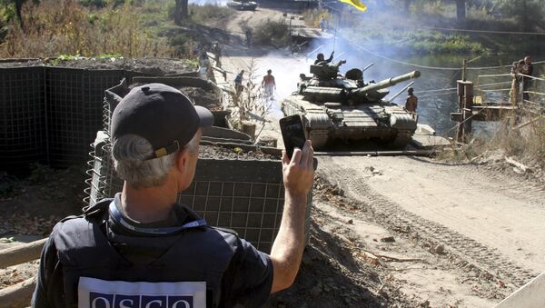A member of the Organization for Security and Co-operation in Europe (OSCE) monitors the withdrawal of tanks of the Ukrainian armed forces near the village of Nyzhnje in Luhansk region, Ukraine, October 5, 2015 - Sputnik International