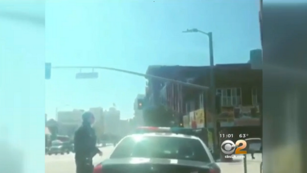 The video footage, posted on social media, begins with a Los Angeles police officer getting out of his patrol car, followed by a shot of a handgun held by a person watching the officer. - Sputnik International