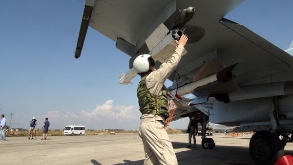In this photo taken on Monday, Oct. 5, 2015, a Russian pilot fixes an air-to-air missile at his Su-30 jet fighter before a take off at Hmeimim airbase in Syria - Sputnik International