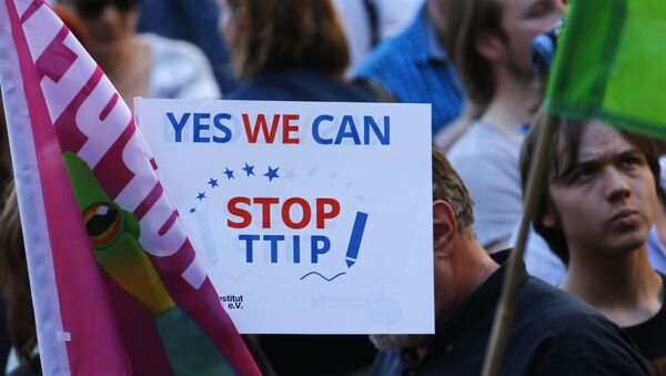 Demonstrators hold a sign against the TTIP contract during a protest against the upcoming G-7 in Munich, southern Germany, Thursday, June 4, 2015 - Sputnik International