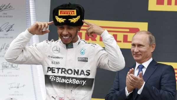 Russian President Vladimir Putin (R) watches as Mercedes Formula One driver Lewis Hamilton of Britain celebrates after winning the Russian F1 Grand Prix in Sochi, Russia, October 11, 2015 - Sputnik International