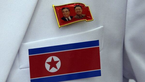 In this Friday, Sept. 12, 2014 photo, a pin of late North Korea leaders Kim Il Sung and Kim Jong Il and North Korea's flag are displayed on a North Korean reporter's jacket at the Main Media Center for the 17th Asian Games in Incheon, west of Seoul, South Korea - Sputnik International